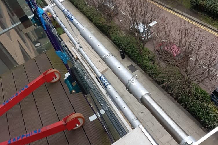 replacing vandalised glass on balcony in Greenwich using specialist equipment